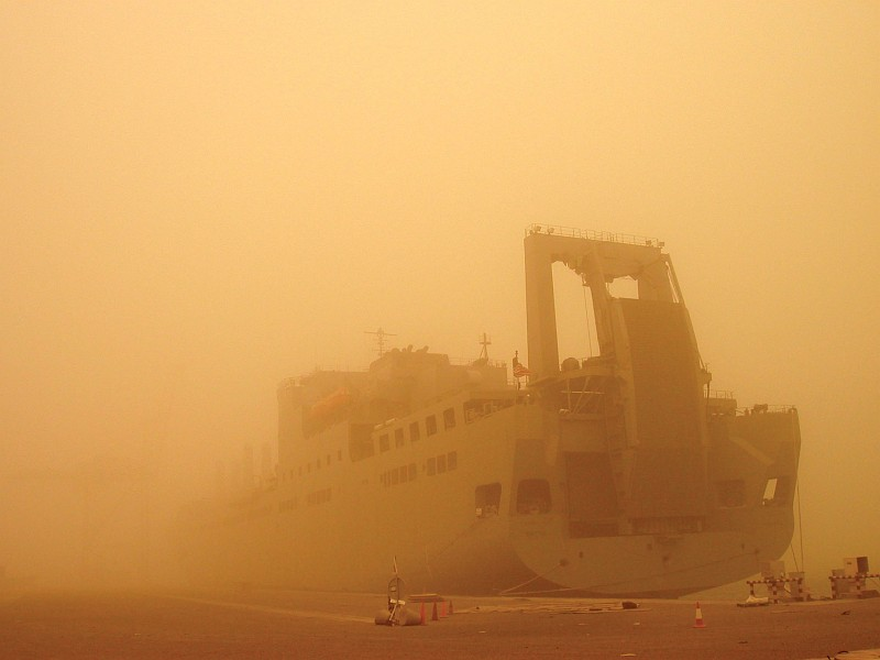 8. USNS Brittin (T-AKR 305) is a United States Navy Military Sealift Command Large, Medium-Speed Roll-on/Roll-off Ship (LMSR), But This Windstorm Generates a Sandstorm That Is So Huge It Significantly Blocks (Filters) the Sun's Rays -- Casting a Yellow-Orange Hue Everywhere -- and Dramatically Obscures Much of the Docked Ship, 2003, Port of Ash Shuaybah, Dawlat al Kuwayt - State of Kuwait. Photo Credit: Military Sealift Command: 2003 in Review (http://www.msc.navy.mil/annualreport/2003/organization.htm) and Sealift, May 2003: 'MSC ships, crews deliver to inhospitable places' (http://www.msc.navy.mil/sealift/2003/May/inhospitable.htm), Military Sealift Command (MSC, http://www.msc.navy.mil), United States Navy (USN, http://www.navy.mil), United States Department of Defense (DoD, http://www.DefenseLink.mil or http://www.dod.gov), Government of the United States of America (USA).