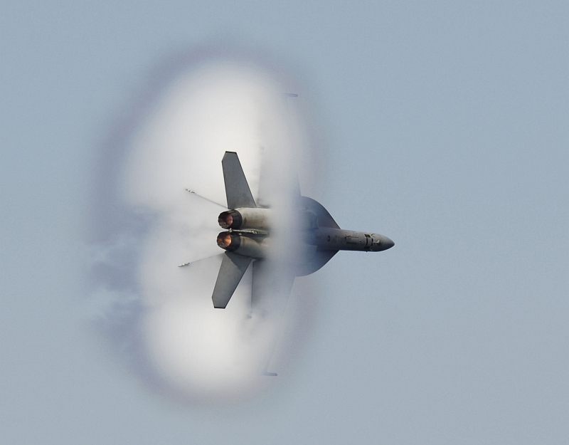 1. An F/A-18F Super Hornet Fighter Jet Assigned to the 'Diamondbacks' of Strike Fighter Squadron One Zero Two (VFA-102), USS Kitty Hawk (CV 63), United States Navy, Off the Coast of Southern Japan, November 5, 2006, Pacific Ocean. Flying at transonic speeds (flying transonically) -- speeds varying near and at the speed of sound (supersonic) -- can generate impressive condensation clouds caused by the Prandtl-Glauert Singularity. For a scientific explanation, see Professor M. S. Cramer's Gallery of Fluid Mechanics, Prandtl-Glauert Singularity at <http://www.GalleryOfFluidMechanics.com/conden/pg_sing.htm>; and Foundations of Fluid Mechanics, Navier-Stokes Equations Potential Flows: Prandtl-Glauert Similarity Laws at <http://www.Navier-Stokes.net/nspfsim.htm>. Photo Credit: Mass Communication Specialist 3rd Class Jarod Hodge, United States Navy (USN, http://www.navy.mil); Defense Visual Information Center (DVIC, http://www.DoDMedia.osd.mil, 061105-N-8591H-389) and United States Navy (USN, http://www.navy.mil), United States Department of Defense (DoD, http://www.DefenseLink.mil or http://www.dod.gov), Government of the United States of America (USA).