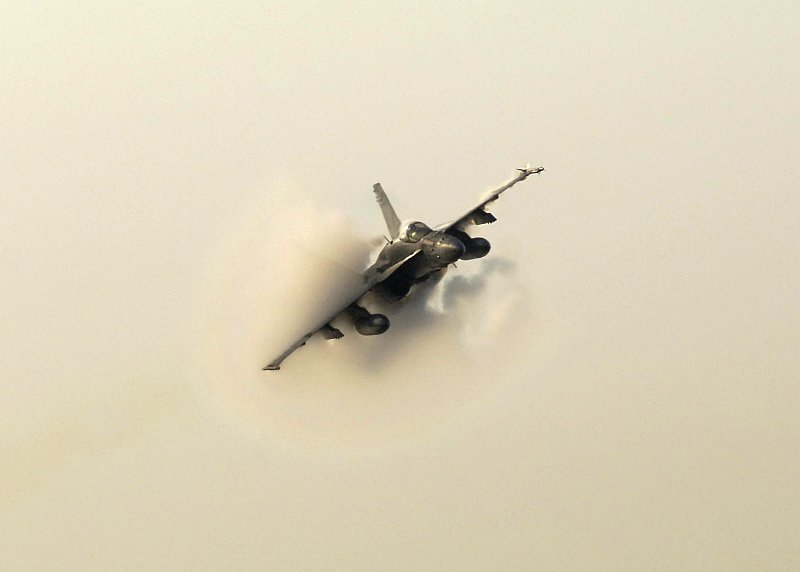 2. An F/A-18C Hornet Fighter Jet Assigned to the 'Sidewinders' of Strike Fighter Squadron Eight Six (VFA-86), USS Enterprise (CVN 65), United States Navy, October 24, 2006, Gulf of Oman. Flying at transonic speeds (flying transonically) -- speeds varying near and at the speed of sound (supersonic) -- can generate impressive condensation clouds caused by the Prandtl-Glauert Singularity. For a scientific explanation, see Professor M. S. Cramer's Gallery of Fluid Mechanics, Prandtl-Glauert Singularity at <http://www.GalleryOfFluidMechanics.com/conden/pg_sing.htm>; and Foundations of Fluid Mechanics, Navier-Stokes Equations Potential Flows: Prandtl-Glauert Similarity Laws at <http://www.Navier-Stokes.net/nspfsim.htm>. Photo Credit: Mass Communication Specialist 2nd Class Milosz Reterski, Navy NewsStand - Eye on the Fleet Photo Gallery (http://www.news.navy.mil/view_photos.asp, 061024-N-9742R-028), United States Navy (USN, http://www.navy.mil), United States Department of Defense (DoD, http://www.DefenseLink.mil or http://www.dod.gov), Government of the United States of America (USA).