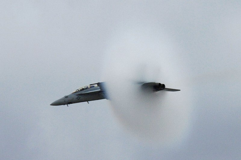 3. An F/A-18F Super Hornet Fighter Jet Assigned to the 'Screaming Eagles' of Strike Fighter Squadron One Two Two (VFA-122), Miramar Air Show, October 15, 2006, Marine Corps Air Station Miramar, San Diego, State of California, USA. Flying at transonic speeds (flying transonically) -- speeds varying near and at the speed of sound (supersonic) -- can generate impressive condensation clouds caused by the Prandtl-Glauert Singularity. For a scientific explanation, see Professor M. S. Cramer's Gallery of Fluid Mechanics, Prandtl-Glauert Singularity at <http://www.GalleryOfFluidMechanics.com/conden/pg_sing.htm>; and Foundations of Fluid Mechanics, Navier-Stokes Equations Potential Flows: Prandtl-Glauert Similarity Laws at <http://www.Navier-Stokes.net/nspfsim.htm>. Photo Credit: Mass Communication Specialist 2nd Class Scott Taylor, Navy NewsStand - Eye on the Fleet Photo Gallery (http://www.news.navy.mil/view_photos.asp, 061015-N-9500T-008), United States Navy (USN, http://www.navy.mil), United States Department of Defense (DoD, http://www.DefenseLink.mil or http://www.dod.gov), Government of the United States of America (USA).