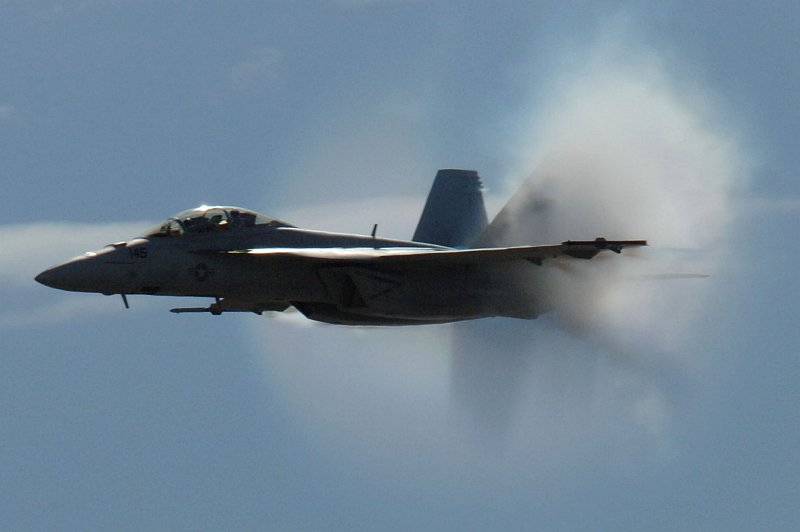4. An F/A-18F Super Hornet Fighter Jet Assigned to the 'Screaming Eagles' of Strike Fighter Squadron One Two Two (VFA-122), Miramar Air Show, October 13, 2006, Marine Corps Air Station Miramar, San Diego, State of California, USA. Flying at transonic speeds (flying transonically) -- speeds varying near and at the speed of sound (supersonic) -- can generate impressive condensation clouds caused by the Prandtl-Glauert Singularity. For a scientific explanation, see Professor M. S. Cramer's Gallery of Fluid Mechanics, Prandtl-Glauert Singularity at <http://www.GalleryOfFluidMechanics.com/conden/pg_sing.htm>; and Foundations of Fluid Mechanics, Navier-Stokes Equations Potential Flows: Prandtl-Glauert Similarity Laws at <http://www.Navier-Stokes.net/nspfsim.htm>. Photo Credit: Mass Communication Specialist 2nd Class Scott Taylor, Navy NewsStand - Eye on the Fleet Photo Gallery (http://www.news.navy.mil/view_photos.asp, 061013-N-9500T-008), United States Navy (USN, http://www.navy.mil), United States Department of Defense (DoD, http://www.DefenseLink.mil or http://www.dod.gov), Government of the United States of America (USA).