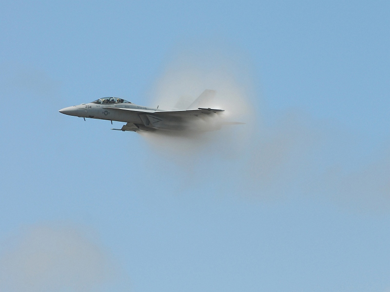 11. A Transonic F/A-18F Super Hornet Fighter Jet Assigned to the 'Checkmates' of Strike Fighter Squadron Two One One (VFA-211), 2007 Naval Air Station Oceana Air Show, Naval Air Station Oceana, September 9, 2007, Virginia Beach, Commonwealth of Virginia, USA. Flying at transonic speeds (flying transonically) -- speeds varying near and at the speed of sound (supersonic) -- can generate impressive condensation clouds caused by the Prandtl-Glauert Singularity. For a scientific explanation, see Professor M. S. Cramer's Gallery of Fluid Mechanics, Prandtl-Glauert Singularity at <http://www.GalleryOfFluidMechanics.com/conden/pg_sing.htm>; and Foundations of Fluid Mechanics, Navier-Stokes Equations Potential Flows: Prandtl-Glauert Similarity Laws at <http://www.Navier-Stokes.net/nspfsim.htm>. Photo Credit: Mass Communication Specialist Seaman Joshua Nuzzo, United States Navy (USN, http://www.navy.mil); Defense Visual Information Center (DVIC, http://www.DoDMedia.osd.mil, 070909-N-4515N-438) and United States Navy (USN, http://www.navy.mil), United States Department of Defense (DoD, http://www.DefenseLink.mil or http://www.dod.gov), Government of the United States of America (USA).