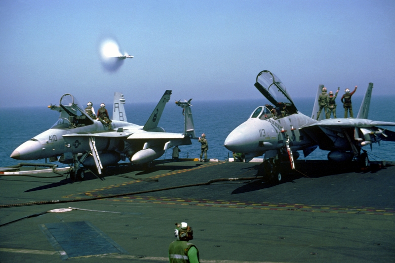 14. A Transonic U.S. Navy F-14A Tomcat Fighter Jet Assigned to Fighter Squadron 102 (VF-102) Conducts A High-Speed Flyby Near the U.S. Navy Aircraft Carrier USS America (CV-66), March 1, 1991, Red Sea. Photo Credit: LCDR Ken Neubauer, United States Navy; Defense Visual Information (DVI, http://www.DefenseImagery.mil, DN-SC-92-02756) and United States Navy (USN, http://www.af.mil), United States Department of Defense (DoD, http://www.DefenseLink.mil or http://www.dod.gov), Government of the United States of America (USA).