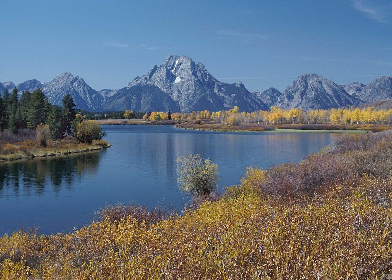 Scenic View of Mountain Peaks, Trees In Autumn (Fall Season) Colors, Evergreen Trees, and the Snake River Outside Jackson, State of Wyoming, USA. Photo Credit: Tim McCabe (1992, http://photogallery.nrcs.usda.gov, NRCSWY92004), USDA Natural Resources Conservation Service (NRCS, http://www.nrcs.usda.gov), United States Department of Agriculture (USDA, http://www.usda.gov), Government of the United States of America (USA).
