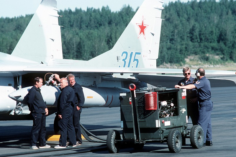 4. USSR and USA Maintenance Personnel Refuel a Soviet MiG-29 Fighter Jet (Tail Number 315), August 1989, Elmendorf Air Force Base, State of Alaska, USA. Photo Credit: Sgt. Gregory A. Suhay, United States Air Force (USAF, http://www.af.mil); Defense Visual Information Center (DVIC, http://www.DoDMedia.osd.mil, DFST9005770) and United States Air Force (USAF, http://www.af.mil), United States Department of Defense (DoD, http://www.DefenseLink.mil or http://www.dod.gov), Government of the United States of America (USA).