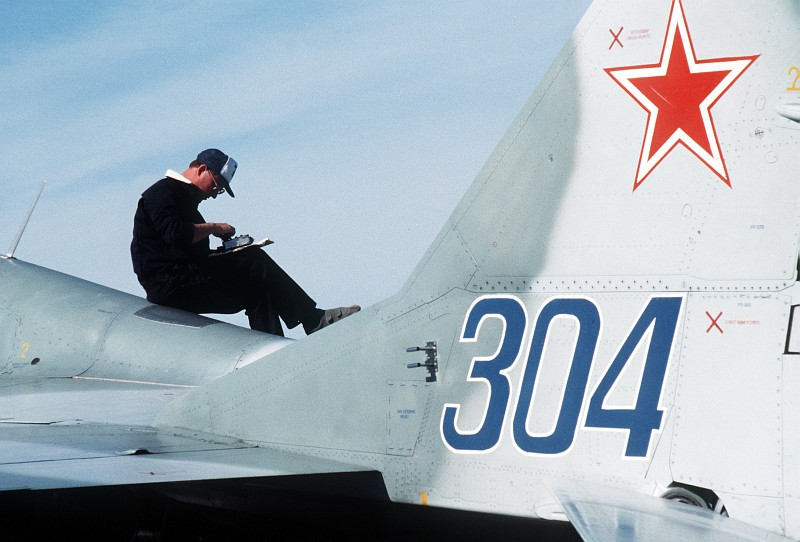 5. A USSR Technician Works While Sitting On Top of the Soviet MiG-29 Fighter (Tail Number 304) as the Aircraft Is Refueled, August 1989, Elmendorf Air Force Base, State of Alaska, USA. Photo Credit: SSgt. Kevin L. Bishop, United States Air Force (USAF, http://www.af.mil); Defense Visual Information Center (DVIC, http://www.DoDMedia.osd.mil, DFST9005762) and United States Air Force (USAF, http://www.af.mil), United States Department of Defense (DoD, http://www.DefenseLink.mil or http://www.dod.gov), Government of the United States of America (USA).