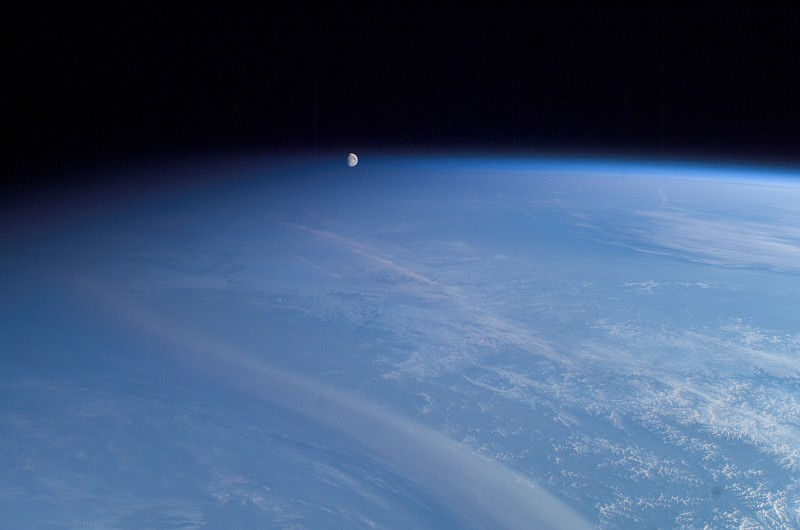 61. It's a Spectacular, Beautiful, and Scenic View of Planet Earth -- Pitch Black Night Approaching From the Left, Moonset Over a Blue Atmosphere Above Earth's Terminator and Horizon, Broad Daylight to the Right Over Cloudly Skies -- On May 11, 2003, at 20:03:04 UTC (GMT) as the International Space Station (Expedition 7) Silently Travels High Above and Across Rossiyskaya Federatsiya - Russian Federation. Photo Credit: ISS007-E-5379, Night to the right, Earth's terminator, Full daylight to the right, Setting of Earth's moon, International Space Station (Expedition Seven) over Russia; Image Science and Analysis Laboratory, NASA-Johnson Space Center. 'Astronaut Photography of Earth - Display Record.' <http://eol.jsc.nasa.gov/scripts/sseop/photo.pl?mission=ISS007&roll=E&frame=5379>; National Aeronautics and Space Administration (NASA, http://www.nasa.gov), Government of the United States of America (USA). In the photo caption <http://eol.jsc.nasa.gov/scripts/sseop/photo.pl?mission=ISS007&roll=E&frame=5379> NASA describes this impressive picture: The moon is really a quarter of a million [250,000] miles away. The picture is tricky because of its uneven lighting. The sun's elevation angle is only 6 [six] degrees. On the left side of the image, night is falling; on the right side, it's still broad daylight. This gradient of sunlight is the key to the illusion.