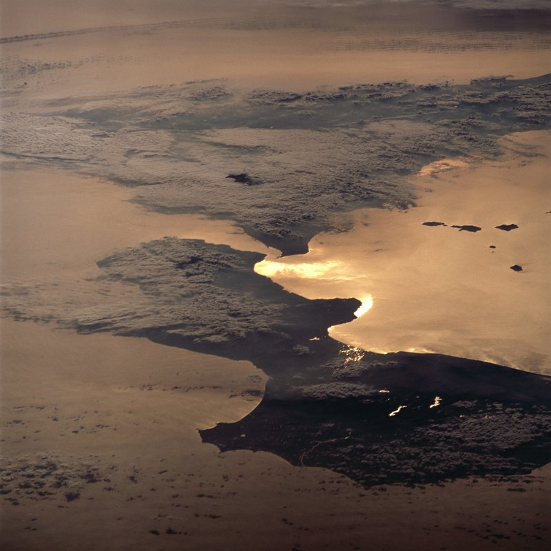 62. The Sun's Late Afternoon Rays Reflect Off the Waters of the Strait of Messina Giving the Appearance of Liquid Gold On February 15, 2001 at 14:36:13 UTC (GMT) -- A Beautiful View Seen From Space Shuttle Atlantis (STS-98) While Over Repubblica Italiana - Italian Republic. Photo Credit: STS098-713-11, Bright sunglint (reflected sunlight) on the Strait of Messina, Space Shuttle Atlantis (STS-98) over Italy; Image Science and Analysis Laboratory, NASA-Johnson Space Center. 'Astronaut Photography of Earth - Display Record.' <http://eol.jsc.nasa.gov/scripts/sseop/photo.pl?mission=STS098&roll=713&frame=11>; National Aeronautics and Space Administration (NASA, http://www.nasa.gov), Government of the United States of America (USA).