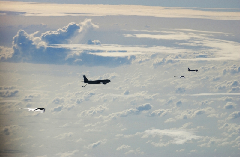 Operation Iraqi Freedom: High Above the Clouds, Two U.S. Air Force KC-135 Stratotankers (From the 28th Expeditionary Air Refueling Squadron) Prepare to Refuel Two U.S. Air Force B-2 Spirit Stealth Bombers (Forward Deployed With the 40th Air Expeditionary Wing), March 21, 2003. Photo Credit: MSgt. Timothy Lancaster, United States Air Force; Defense Visual Information (DVI, http://www.DefenseImagery.mil, 030321-F-DC852-003) and United States Air Force (USAF, http://www.af.mil), United States Department of Defense (DoD, http://www.DefenseLink.mil or http://www.dod.gov), Government of the United States of America (USA).