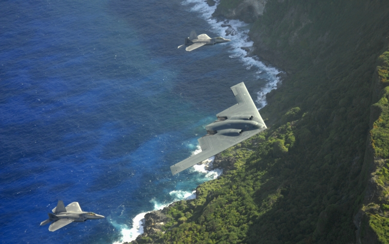 2. The B-2 Spirit and Two F-22A Raptors Fly In Formation Above As Waves From the Pacific Ocean Crash On The Rocks Below, April 14, 2009, Territory of Guam, USA. Photo Credit: Master Sgt. Kevin J. Gruenwald, United States Air Force (USAF, http://www.af.mil); Defense Visual Information (DVI, http://www.DefenseImagery.mil, 090414-F-6911G-001) and United States Air Force (USAF, http://www.af.mil), United States Department of Defense (DoD, http://www.DefenseLink.mil or http://www.dod.gov), Government of the United States of America (USA).