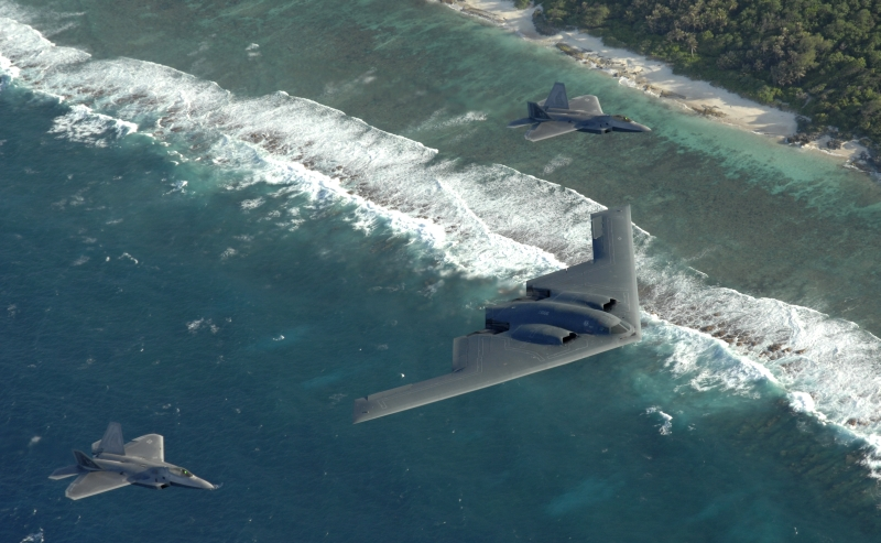 6. With the Sandy Coastline In View, Two F-22A Raptor Fighter Jets and One B-2 Spirit Stealth Bomber Fly In Formation Over the Pacific Ocean, April 7, 2009, Territory of Guam, USA. Photo Credit: Master Sgt. Kevin J. Gruenwald, United States Air Force; Defense Visual Information (DVI, http://www.DefenseImagery.mil, 090414-F-6911G-003) and United States Air Force (USAF, http://www.af.mil), United States Department of Defense (DoD, http://www.DefenseLink.mil or http://www.dod.gov), Government of the United States of America (USA).