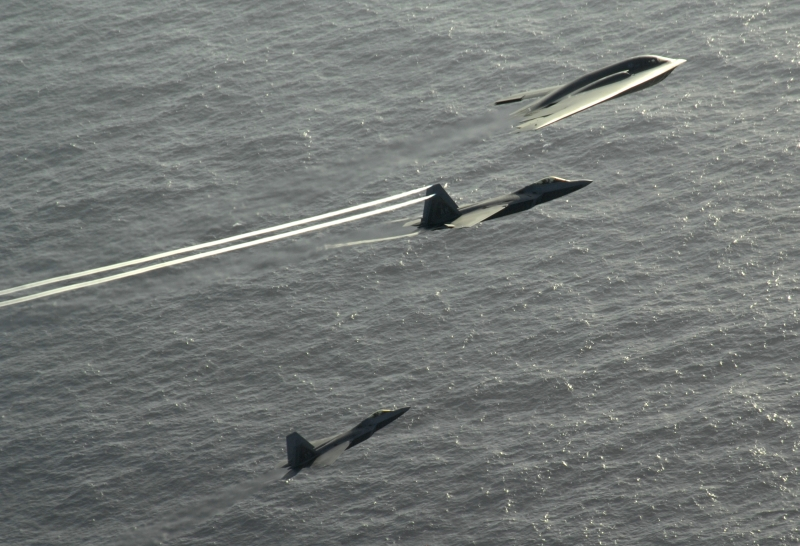 5. The B-2 Spirit and the Two F-22A Raptor Fighter Jets -- the Center Aircraft, An F-22A Raptor, With Trailing Vortices -- Flying In Formation Over the Pacific Ocean, April 7, 2009, Territory of Guam, USA. Photo Credit: Master Sgt. Kevin J. Gruenwald, United States Air Force; Defense Visual Information (DVI, http://www.DefenseImagery.mil, 090414-F-6911G-005) and United States Air Force (USAF, http://www.af.mil), United States Department of Defense (DoD, http://www.DefenseLink.mil or http://www.dod.gov), Government of the United States of America (USA).