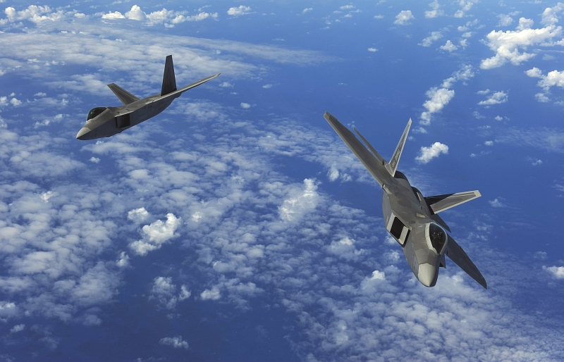 28. Two U.S. Air Force F-22A Raptor Stealth Fighter Jets Fly Over the Western Pacific Ocean, February 16, 2010, Territory of Guam, USA. Photo Credit: Staff Sgt. Jacob N. Bailey, United States Air Force; Defense Visual Information (DVI, http://www.DefenseImagery.mil, 100216-F-5964B-544) and United States Air Force (USAF, http://www.af.mil), United States Department of Defense (DoD, http://www.DefenseLink.mil or http://www.dod.gov), Government of the United States of America (USA).