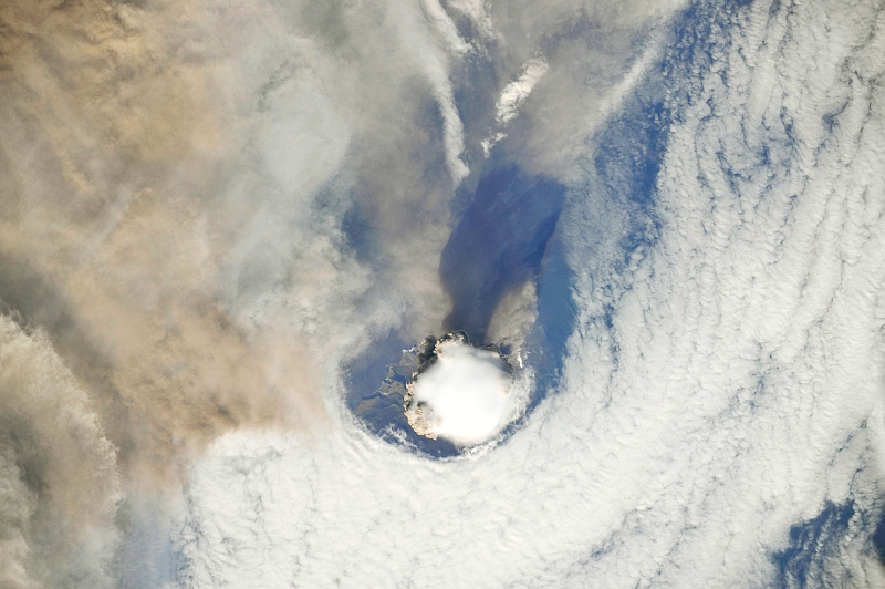 1. Sarychev Peak Volcano Erupts -- Clearing,  Possibly From Its Shock Wave, A Circle In the Cloud Deck Above -- With A Plume of Brown Ash and Steam, June 12, 2009 at 22:15:25 GMT, Matua Island, Kuril Islands, Rossiyskaya Federatsiya -- Russian Federation, As Seen From the International Space Station (Expedition 20) Photo Credit: NASA, International Space Station (Expedition Twenty); ISS020-E-8737, Sarychev Peak, Invisible shock wave, Volcanic plume, Matua Island, Kuril (or Kurile) Islands; Image Science and Analysis Laboratory, NASA-Johnson Space Center. 'Astronaut Photography of Earth - Display Record.' <http://eol.jsc.nasa.gov/scripts/sseop/photo.pl?mission=ISS020&roll=E&frame=8737>; National Aeronautics and Space Administration (NASA, http://www.nasa.gov), Government of the United States of America (USA).