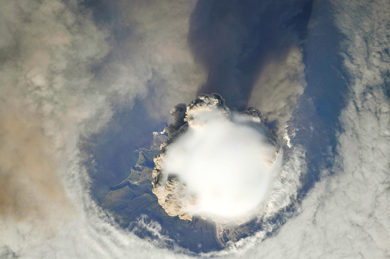 2. Sarychev Peak Volcano Erupts -- Clearing,  Possibly From Its Shock Wave, A Circle In the Cloud Deck Above -- With A Plume of Brown Ash and Steam, June 12, 2009 at 22:15:28 GMT, Matua Island, Kuril Islands, Rossiyskaya Federatsiya -- Russian Federation, As Seen From the International Space Station (Expedition 20) Photo Credit: NASA, International Space Station (Expedition Twenty); ISS020-E-8737, Sarychev Peak, Invisible shock wave, Volcanic plume, Matua Island, Kuril (or Kurile) Islands; Image Science and Analysis Laboratory, NASA-Johnson Space Center. 'Astronaut Photography of Earth - Display Record.' <http://eol.jsc.nasa.gov/scripts/sseop/photo.pl?mission=ISS020&roll=E&frame=8738>; National Aeronautics and Space Administration (NASA, http://www.nasa.gov), Government of the United States of America (USA).