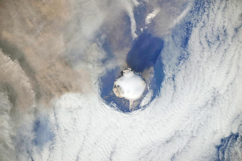 3. Sarychev Peak Volcano Erupts -- Clearing,  Possibly From Its Shock Wave, A Circle In the Cloud Deck Above -- With A Plume of Brown Ash and Steam, June 12, 2009 at 22:15:35 GMT, Matua Island, Kuril Islands, Rossiyskaya Federatsiya -- Russian Federation, As Seen From the International Space Station (Expedition 20) Photo Credit: NASA, International Space Station (Expedition Twenty); ISS020-E-8743, Sarychev Peak, Invisible shock wave, Volcanic plume, Matua Island, Kuril (or Kurile) Islands; Image Science and Analysis Laboratory, NASA-Johnson Space Center. 'Astronaut Photography of Earth - Display Record.' <http://eol.jsc.nasa.gov/scripts/sseop/photo.pl?mission=ISS020&roll=E&frame=8743>; National Aeronautics and Space Administration (NASA, http://www.nasa.gov), Government of the United States of America (USA).
