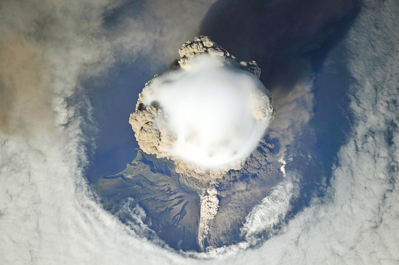 4. Sarychev Peak Volcano Erupts -- Clearing,  Possibly From Its Shock Wave, A Circle In the Cloud Deck Above -- With A Plume of Brown Ash and Steam, June 12, 2009 at 22:15:45 GMT, Matua Island, Kuril Islands, Rossiyskaya Federatsiya -- Russian Federation, As Seen From the International Space Station (Expedition 20) Photo Credit: NASA, International Space Station (Expedition Twenty); ISS020-E-8747, Sarychev Peak, Invisible shock wave, Volcanic plume, Matua Island, Kuril (or Kurile) Islands; Image Science and Analysis Laboratory, NASA-Johnson Space Center. 'Astronaut Photography of Earth - Display Record.' <http://eol.jsc.nasa.gov/scripts/sseop/photo.pl?mission=ISS020&roll=E&frame=8747>; National Aeronautics and Space Administration (NASA, http://www.nasa.gov), Government of the United States of America (USA).