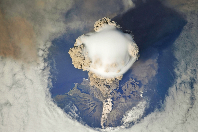 5. Sarychev Peak Volcano Erupts -- Clearing,  Possibly From Its Shock Wave, A Circle In the Cloud Deck Above -- With A Plume of Brown Ash and Steam, June 12, 2009 at 22:15:55 GMT, Matua Island, Kuril Islands, Rossiyskaya Federatsiya -- Russian Federation, As Seen From the International Space Station (Expedition 20) Photo Credit: NASA, International Space Station (Expedition Twenty); ISS020-E-8750, Sarychev Peak, Invisible shock wave, Volcanic plume, Matua Island, Kuril (or Kurile) Islands; Image Science and Analysis Laboratory, NASA-Johnson Space Center. 'Astronaut Photography of Earth - Display Record.' <http://eol.jsc.nasa.gov/scripts/sseop/photo.pl?mission=ISS020&roll=E&frame=8750>; National Aeronautics and Space Administration (NASA, http://www.nasa.gov), Government of the United States of America (USA).