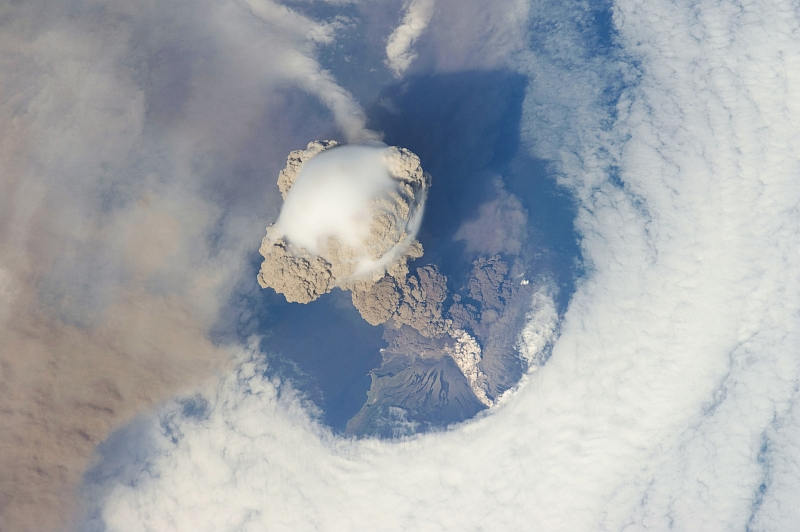 6. Sarychev Peak Volcano Erupts -- Clearing,  Possibly From Its Shock Wave, A Circle In the Cloud Deck Above -- With A Plume of Brown Ash and Steam, June 12, 2009 at 22:16:14 GMT, Matua Island, Kuril Islands, Rossiyskaya Federatsiya -- Russian Federation, As Seen From the International Space Station (Expedition 20) Photo Credit: NASA, International Space Station (Expedition Twenty); ISS020-E-9048, Sarychev Peak, Invisible shock wave, Volcanic plume, Matua Island, Kuril (or Kurile) Islands; Image Science and Analysis Laboratory, NASA-Johnson Space Center. 'Astronaut Photography of Earth - Display Record.' <http://eol.jsc.nasa.gov/scripts/sseop/photo.pl?mission=ISS020&roll=E&frame=9048>; National Aeronautics and Space Administration (NASA, http://www.nasa.gov), Government of the United States of America (USA).