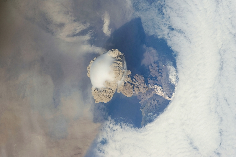 7. Sarychev Peak Volcano Erupts -- Clearing,  Possibly From Its Shock Wave, A Circle In the Cloud Deck Above -- With A Plume of Brown Ash and Steam, June 12, 2009 at 22:16:21 GMT, Matua Island, Kuril Islands, Rossiyskaya Federatsiya -- Russian Federation, As Seen From the International Space Station (Expedition 20) Photo Credit: NASA, International Space Station (Expedition Twenty); ISS020-E-9052, Sarychev Peak, Invisible shock wave, Volcanic plume, Ash cloud, Matua Island, Kuril (or Kurile) Islands; Image Science and Analysis Laboratory, NASA-Johnson Space Center. 'Astronaut Photography of Earth - Display Record.' <http://eol.jsc.nasa.gov/scripts/sseop/photo.pl?mission=ISS020&roll=E&frame=9052>; National Aeronautics and Space Administration (NASA, http://www.nasa.gov), Government of the United States of America (USA).