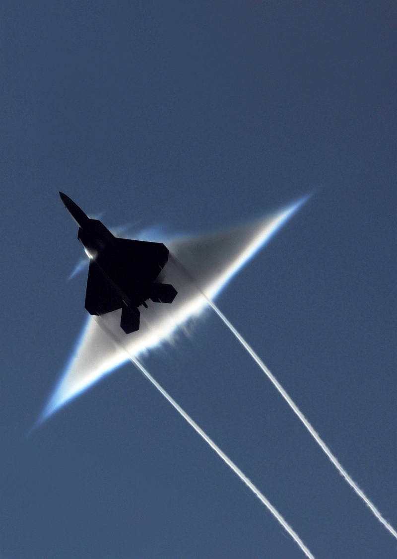 3. Condensation Cloud and Wingtip Vortices: A United States Air Force F-22A Raptor Stealth Fighter Jet, June 22, 2009, High-Speed Flyby Above the United States Navy's Nimitz-Class Aircraft Carrier USS John C. Stennis (CVN 74) During Northern Edge 2009 in the Gulf of Alaska, State of Alaska, USA. Photo Credit: Mass Communication Specialist 2nd Class Kyle Steckler, United States Navy; Defense Visual Information (DVI, http://www.DefenseImagery.mil, 090622-N-7780S-014) and United States Navy (USN, http://www.navy.mil), United States Department of Defense (DoD, http://www.DefenseLink.mil or http://www.dod.gov), Government of the United States of America (USA).