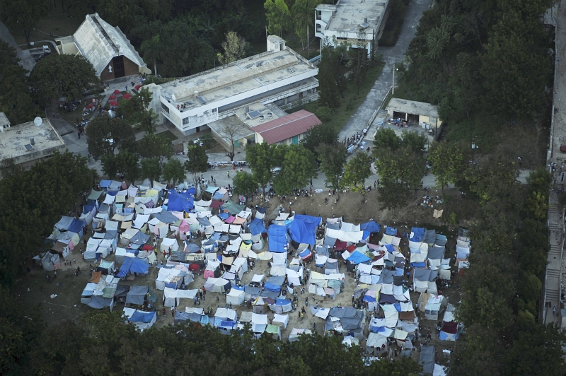 32. Earthquake Survivors At Their Tent Camp, January 15, 2010, Republique d'Haiti (Repiblik d' Ayiti) - Republic of Haiti. Photo Credit: Technical Sgt. (TSgt) James L. Harper Jr., United States Air Force; Defense Visual Information (DVI, http://www.DefenseImagery.mil, 100115-F-4177H-206) and United States Air Force (USAF, http://www.af.mil), United States Department of Defense (DoD, http://www.DefenseLink.mil or http://www.dod.gov), Government of the United States of America (USA).