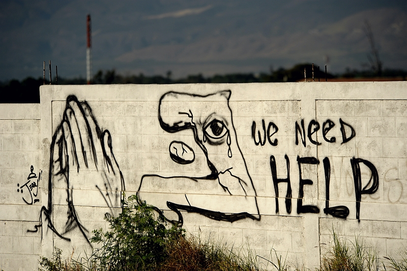 45. Graffiti Painted On the Wall: 'We Need HELP', January 22, 2010, Port-au-Prince, Republique d'Haiti (Repiblik d' Ayiti) - Republic of Haiti.  Photo Credit: Master Sgt. Jeremy Lock, United States Air Force; Defense Visual Information (DVI, http://www.DefenseImagery.mil, 100122-F-1644L-205) and United States Air Force (USAF, http://www.af.mil), United States Department of Defense (DoD, http://www.DefenseLink.mil or http://www.dod.gov), Government of the United States of America (USA).