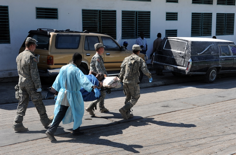 42. Four Men -- Three United States Soldiers and One Man Wearing A Blue Hospital Gown -- Move A Stretcher-Bound Patient To A Medical Care Unit At A Hospital In Port-au-Prince, January 22, 2010, Republique d'Haiti (Repiblik d' Ayiti) - Republic of Haiti. Photo Credit: Technical Sgt. Prentice Colter (TSgt), United States Air Force; Defense Visual Information (DVI, http://www.DefenseImagery.mil, 100122-F-7951C-037) and United States Air Force (USAF, http://www.af.mil), United States Department of Defense (DoD, http://www.DefenseLink.mil or http://www.dod.gov), Government of the United States of America (USA).