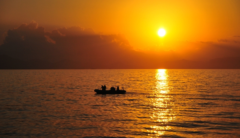 48. Golden Rays From the Sun Reflect Off the Caribbean Sea As Sailors, In A Rigid-Hull Inflatable Boat, Return To the U.S. Navy Guided-Missile Cruiser USS Normandy-CG-60 After An Initial Assessment of Petit-Trou-de-Nippes, January 23, 2010, Republique d'Haiti (Repiblik d' Ayiti) - Republic of Haiti.  Photo Credit: Mass Communication Specialist 3rd Class Samantha Robinett, Navy News Service - Eye on the Fleet (http://www.news.navy.mil/view_photos.asp, 100123-N-4774B-998), United States Navy (USN, http://www.navy.mil), United States Department of Defense (DoD, http://www.DefenseLink.mil or http://www.dod.gov), Government of the United States of America (USA).