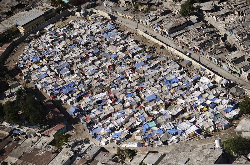 59. A Large Tent City, Packed With Makeshift Shelters, Is Home To Earthquake Survivors and Victims, January 28, 2010, Port-au-Prince, Republique d'Haiti (Repiblik d' Ayiti) - Republic of Haiti. Photo Credit: Mass Communication Specialist 2nd Class Kristopher Wilson, United States Navy; Defense Visual Information (DVI, http://www.DefenseImagery.mil, 100128-N-5345W-266) and United States Navy (USN, http://www.navy.mil), United States Department of Defense (DoD, http://www.DefenseLink.mil or http://www.dod.gov), Government of the United States of America (USA).