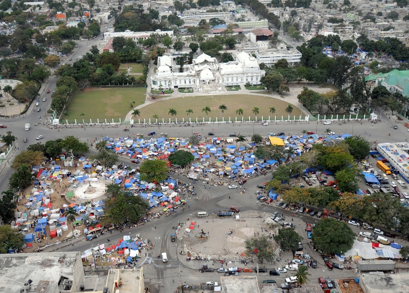 58. Earthquake Survivors Living In A Tent City In Front Of the Earthquake-Damaged Presidential Palace (National Palace), February 1, 2010, Port-au-Prince, Republique d'Haiti (Repiblik d' Ayiti) - Republic of Haiti. Photo Credit: Senior Chief Mass Communication Specialist Spike Call, United States Navy; Defense Visual Information (DVI, http://www.DefenseImagery.mil, 100201-N-5961C-002) and United States Navy (USN, http://www.navy.mil), United States Department of Defense (DoD, http://www.DefenseLink.mil or http://www.dod.gov), Government of the United States of America (USA).