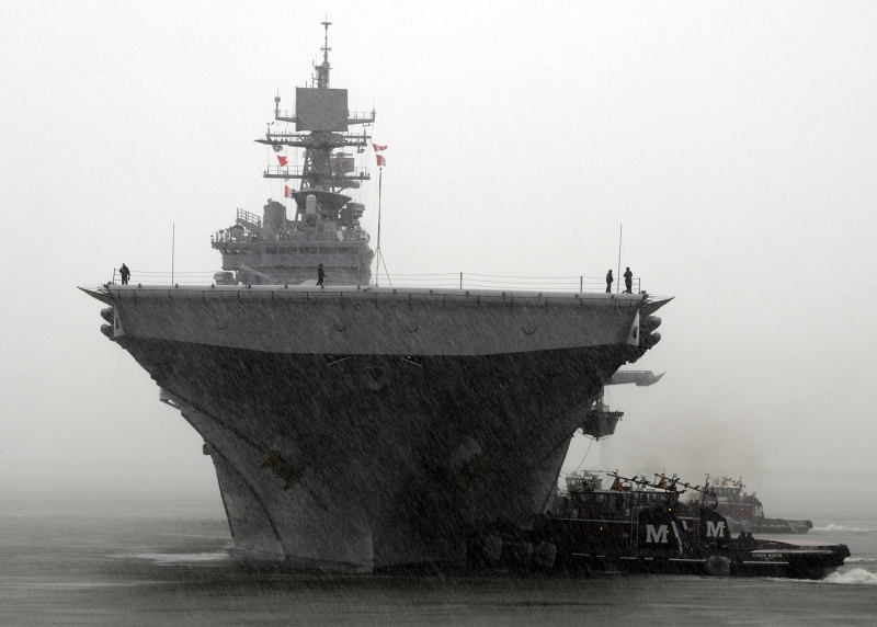 1. The Amphibious Assault Ship USS Bataan (LHD 5) -- In the Rain and Accompanied By Two Tugboats -- Returns to Naval Station Norfolk, May 23, 2013, Commonwealth of Virginia, USA. Photo Credit: Mass Communication Specialist 1st Class Phil Beaufort, Photo Gallery (http://www.navy.mil/viewGallery.asp, 130523-N-ZO696-004), United States Navy (USN, http://www.navy.mil), United States Department of Defense (DoD, http://www.DefenseLink.mil or http://www.dod.gov), Government of the United States of America (USA).