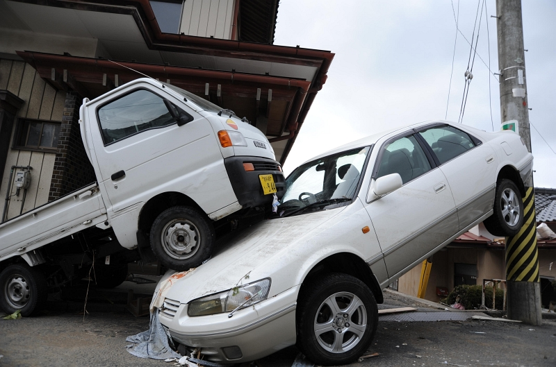 3. A Car Sandwiched Between A Pickup Truck and A Light Pole in Downtown Ofunato, March 15, 2011, Nippon-koku (Nihon-koku) - Japan. Photo Credit: Mass Communication Specialist 1st Class Matthew M. Bradley, United States Navy; Defense Visual Information (DVI, http://www.DefenseImagery.mil, 110315-N-KK192-126) and United States Navy (USN, http://www.navy.mil), United States Department of Defense (DoD, http://www.DefenseLink.mil or http://www.dod.gov), Government of the United States of America (USA).