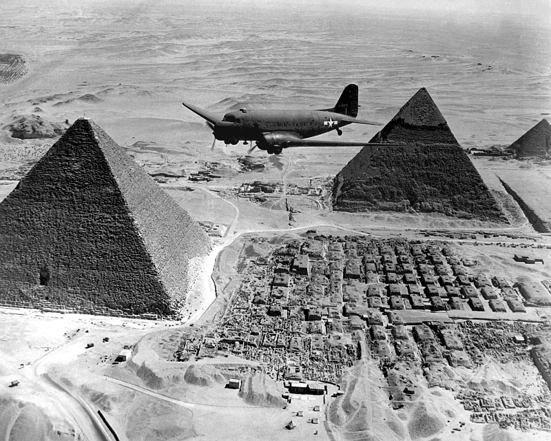 10. An Air Transport Command Plane Flies Over The Pyramids During World War II (WWII), 1943, Jumhuriyat Misr al-Arabiyah - Arab Republic of Egypt. Photo Credit: Defense Visual Information Center (DVIC, http://www.DoDMedia.osd.mil, HD-SN-99-02674, NARA File #: 111-SC-179564), United States Department of Defense (DoD, http://www.DefenseLink.mil or http://www.dod.gov), Government of the United States of America (USA).